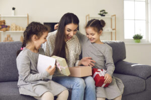 >thisisjustarandomplaceholder<Excited young woman opens the present her little children gave her on Mother's Day   Iberian Press®